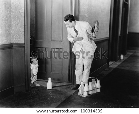 Milkman greeting baby at door - stock photo