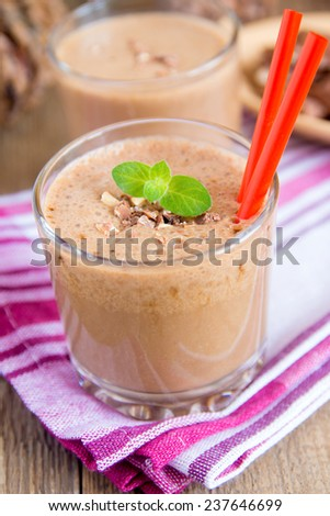 Milkshake (chocolate and banana smoothie) in glass with mint and nuts, homemade dairy breakfast or dessert vertical close up - stock photo