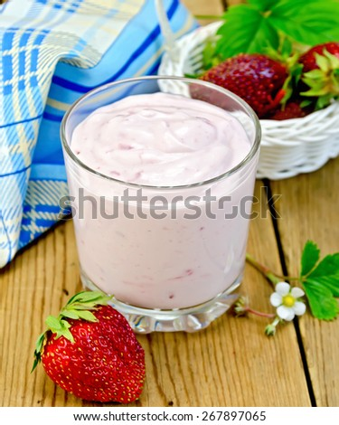 Milkshake in a glass, strawberries in a white wicker basket, flower strawberry with leaves and a napkin on a wooden boards background - stock photo