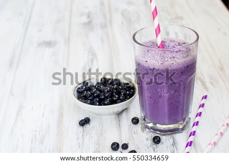 Milkshake in a glass with blueberries, blueberries in a bowl on a white table