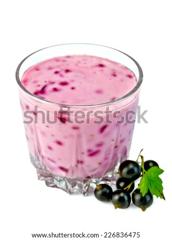 Milkshake in a low glass beaker, berries and green leaves of black currant isolated on white background - stock photo