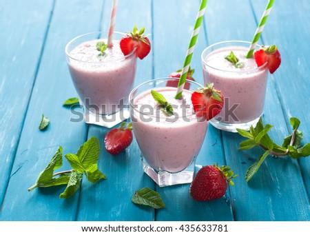 Milkshake. Milkshake with fresh strawberries in a glass jar on blue table. dairy drink. - stock photo
