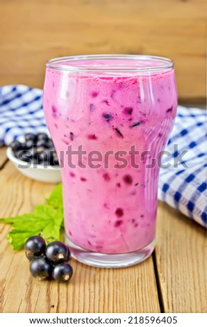 Milkshake with black currants in a glass, a napkin, currants against the background of wooden boards - stock photo