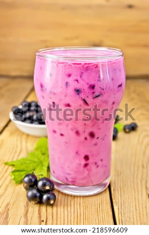 Milkshake with black currants in a glass, currants against the background of wooden boards - stock photo