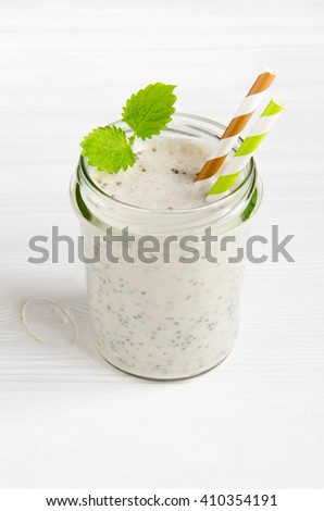 Milkshake with chia seeds in glass jar on white background