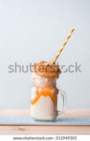 milkshake with salted caramel glazed donut, whipped cream and sweet popcorn - stock photo