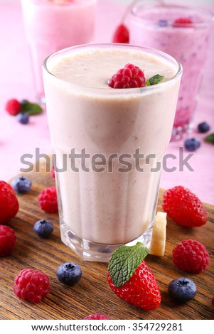 Milkshakes at cutting board with berries on light background, close-up - stock photo