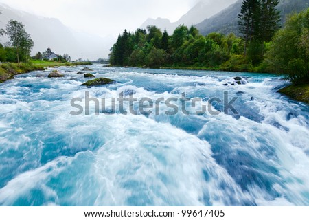 Milky blue glacial water of Briksdal River in Norway - stock photo