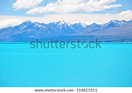 Milky blue water of Lake Pukaki with beautiful view on Southern Alps in the background - stock photo