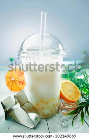 Milky bubble tea blended with fresh orange fruit and boba or tapioca balls served at the sea - stock photo
