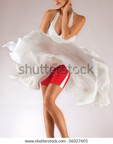 Milky Way. A close-up of a sportive young lady in an airy skirt waving in the breeze. - stock photo