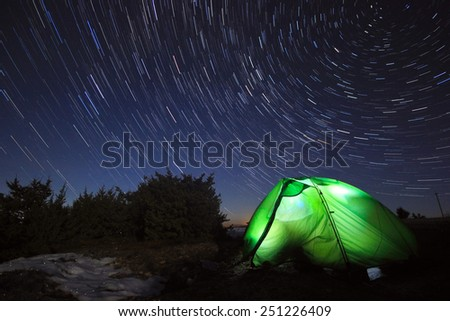 milky way above the mountains with tent highlighted by lamp - stock photo