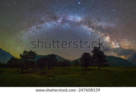 Milky Way arc over mountains - stock photo