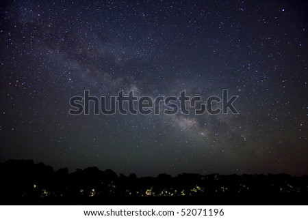 milky way galaxy over road lit by headlights - stock photo