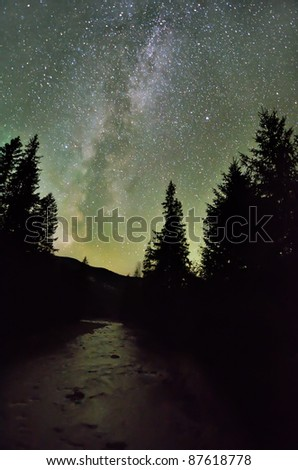 Milky way galaxy over the river and dark forest - stock photo