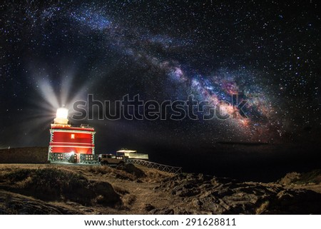 Milky way over a lighthouse - focus is on the lighthouse  - stock photo
