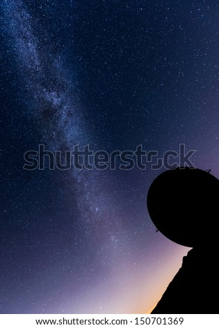 milky way over a radar installation in silhouette - stock photo
