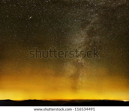 Milky way over black mountains and yellow city lights on starry sky - stock photo
