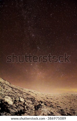 milky way over clouds and snowy hills - stock photo