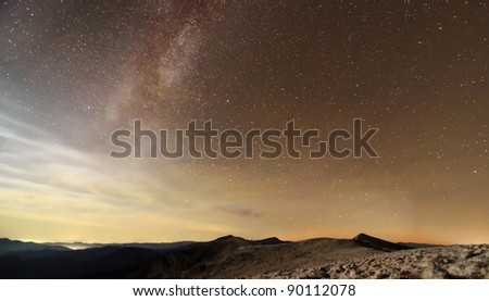 Milky Way over mountains with clouds and moon light - stock photo