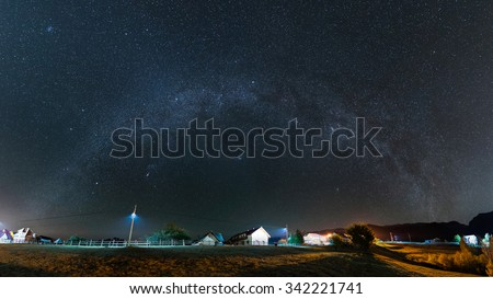 Milky Way over the village at Pestera, Bran, Romania - stock photo