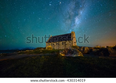Milky Way Rising Above Church Of Good Shepherd, Tekapo NZ with airglow casting visible greenish hues on the sky. Noise due to high ISO; soft focus / shallow DOF due to wide aperture used. - stock photo