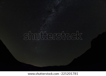 milky way rising above distant valley village - stock photo