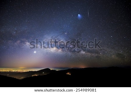 """Milky Way, Rocket, Meteor, Venus, and Zodiacal Lights over Doi Inthanon National Park, Chiang Mai, Thailand.  The blurry blue """"comet"""" on the top right of the image is actually Ariane 5 rocket booster. - stock photo"""