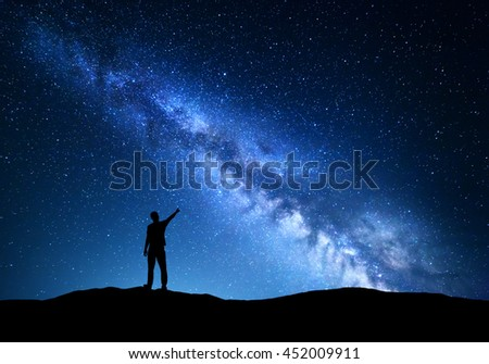 Milky Way. Silhouette of a standing man pointing finger in night starry sky on the mountain. Colorful night landscape with beautiful universe. Travel background with blue sky and amazing Milky Way - stock photo