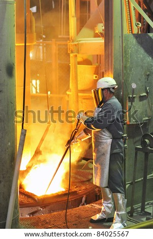 mill worker with hot steel - stock photo