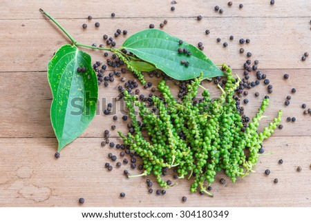 milled black pepper ,Black pepper corns on wood background - stock photo