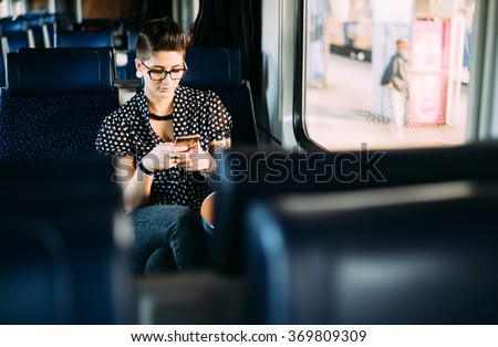 Millenial young woman texting on train - stock photo