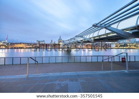 Millennium bridge and St.Paul's cathedral viewed at sunrise in London, England - stock photo