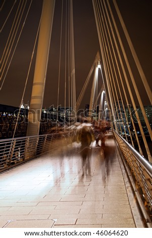 Millennium bridge in London with blurred motion walkers - stock photo
