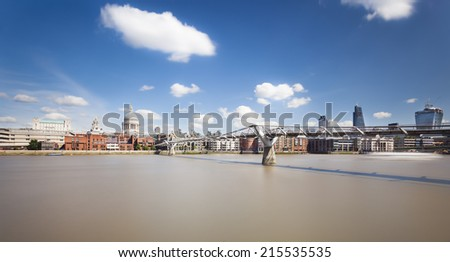 Millennium Bridge in London with St. Paul's Cathedral in the background and a beautiful sky. Long exposure shot. - stock photo