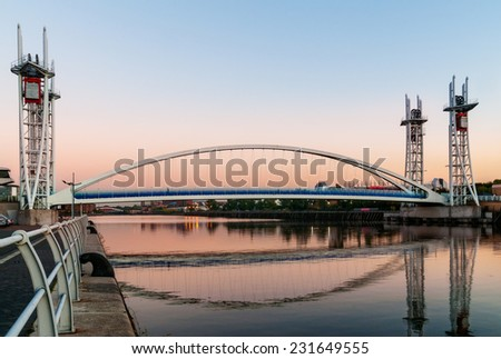 Millennium Bridge or the Lowery Bridge is a lift bridge provides pedestrian over the Manchester Ship Canal. - stock photo