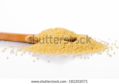 Millet in a wooden spoon isolated on a white background
