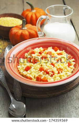 Millet porridge with pumpkin and milk in the plate on the table