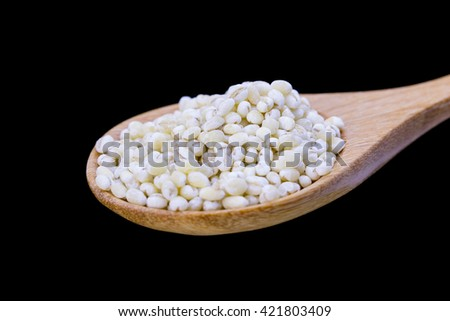 Millet rice, buckwheat in wooden spoon over Black background, Selective focus - stock photo