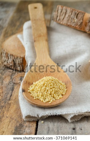 Millet seeds in a wooden spoon