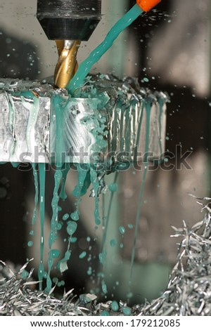 Milling machine is making part while coolant is spraying - stock photo