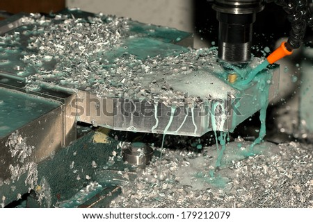 Milling machine making part while coolant is spraying - stock photo
