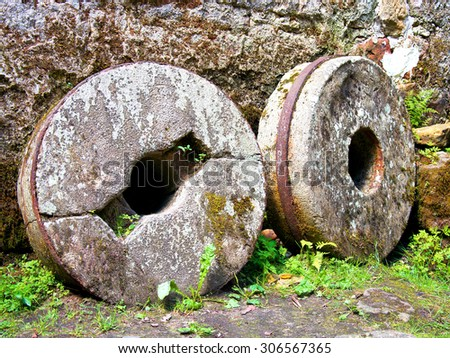 Millstone grinders round in old mill house - stock photo