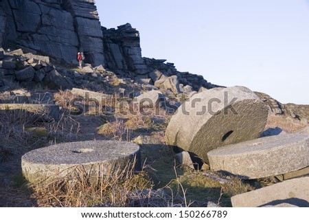 Millstones lie abandoned in situ at the old quarry site at Stanage Edge, Peak District, UK