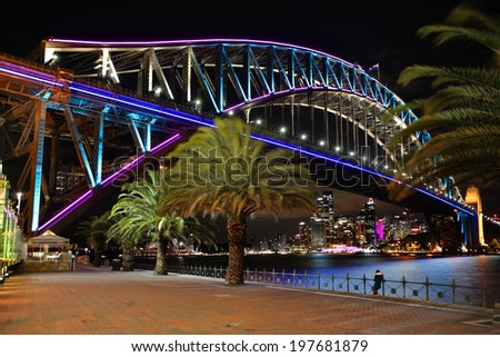 MILSONS POINT SYDNEY, AUSTRALIA - JUNE 7, 2014;  Night vew from the promenade of Sydney Harbour Bridge in pink, blue and aqua during Vivid Sydney annual festival of light, music and ideas. - stock photo