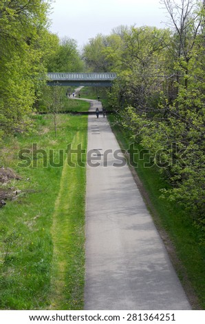 MILWAUKEE - MAY 15, 2015: Bicyclists and walkers on the Oak Leaf trail in Milwaukee. Oak Leaf trail is the crown jewel of Milwaukee County's extensive trail system and meanders more than 100 miles.   - stock photo