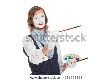 Mime Artist holding brushes and easel portrays painter - stock photo