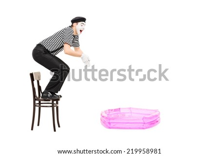 Mime artist jumping into a small inflatable pool isolated on white background - stock photo