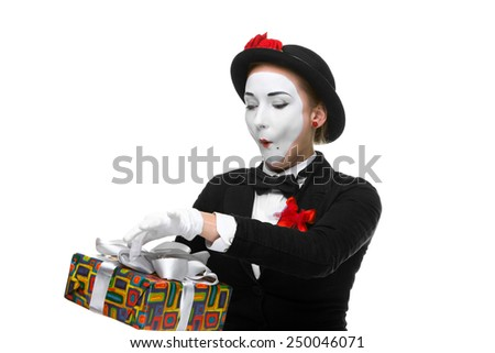 Mime as playful, joyful and excited woman with gift standing isolated on white background.  - stock photo