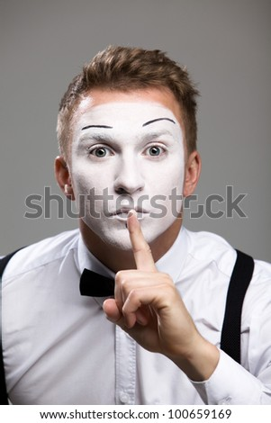 Mime face and hands put his finger to his lips in a theatrical make-up isolated on gray background - stock photo